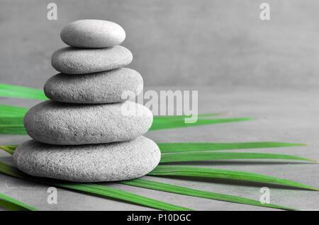 L'équilibre des pierres et le vert feuille de palmier. Concept spa et zen. Banque D'Images