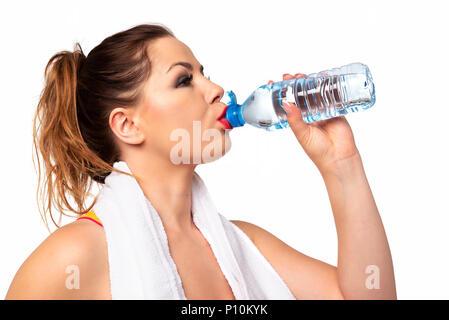L'activité Fitness concept - portrait d'une jeune femme séduisante de l'eau potable au cours de l'entraînement sur un fond blanc. Banque D'Images
