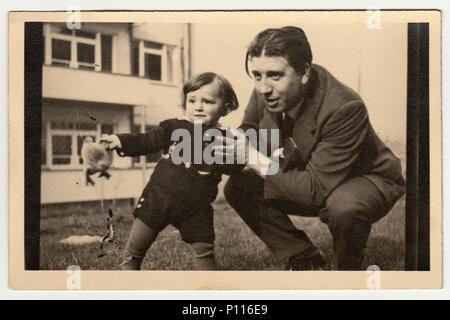 PRAGUE, la République socialiste tchécoslovaque - circa 1950: Vintage photo montre père avec enfant et jouets en peluche (animal en peluche). Banque D'Images