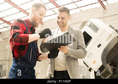 Heureux les hommes dans le service de réparation automobile Banque D'Images