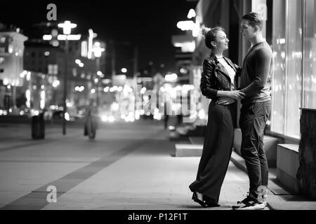 Beau couple sur une date dans une piscine de la ville de nuit Banque D'Images
