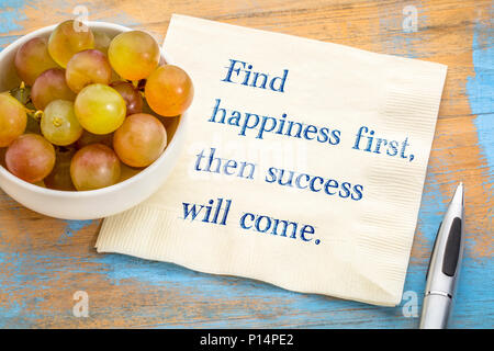 Trouver le bonheur d'abord, puis le succès viendra. Handwriitng d'inspiration sur serviette avec des raisins Banque D'Images