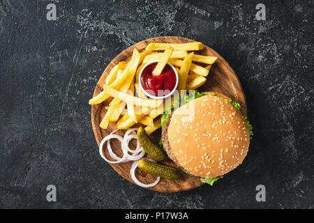 Burger, hamburger ou cheeseburger accompagné de frites, les cornichons et l'oignon sur planche de bois. Vue d'en haut. Concept de restauration rapide Banque D'Images
