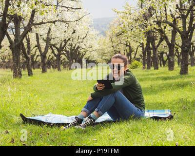 Young attractive woman reading on son ebook à l'extérieur et de rire Banque D'Images