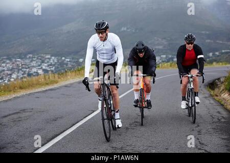 Les cyclistes masculins dédié à vélo sur route en montée Banque D'Images