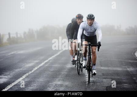 Les cyclistes masculins dédié à vélo sur route pluvieuse Banque D'Images