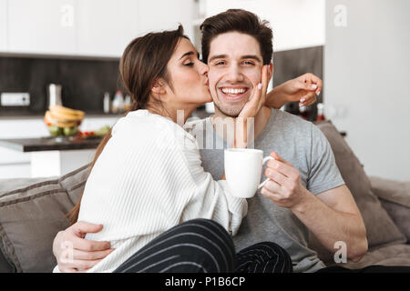 Portrait d'un jeune couple sympathique de boire du café tout en étant assis sur un canapé et s'embrasser Banque D'Images