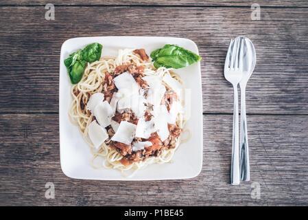 Tourné directement au-dessus de pâtes avec sauce bolognaise, basilic et parmesan râpé sur la table en bois rustique Banque D'Images