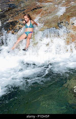 Une jeune fille en glissant sur les rapides à la trois piscines de natation de loisirs de trou dans l'Oregon. Banque D'Images