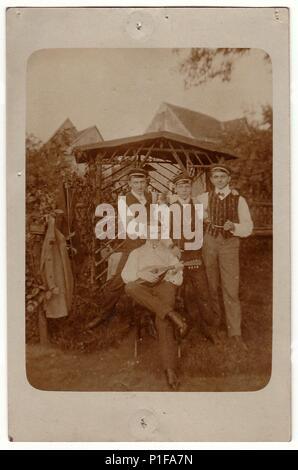 Allemagne - VERS 1920: Vintage photo montre des hommes à l'avant du kiosque. L'un d'eux joue de la mandoline. Meubles anciens photo noir et blanc. En haut et en bas de l'image sont empreintes de punaises. Banque D'Images
