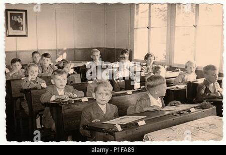 La République socialiste tchécoslovaque - circa 1950: Retro photo montre les élèves passent à l'école en bois d'un bureau dans la salle de classe. Banque D'Images