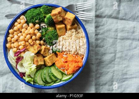 Saladier avec le quinoa, le tofu, les pois chiches et les légumes sur toile de fond textile. Haut afficher, copier du texte pour l'espace Banque D'Images