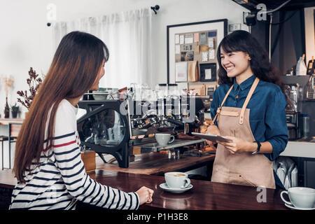 Serveur Barista Asie prendre commande de client dans un café, café propriétaire écrit verre commander au bar comptoir,Nourriture et boisson concept commercial,l'esprit de service Banque D'Images