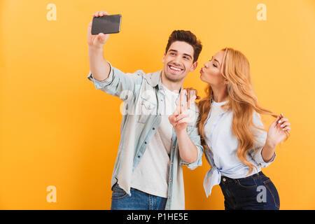 Portrait de joli couple taking photo selfies sur téléphone cellulaire en woman kissing man sur sa joue sur fond jaune isolé Banque D'Images
