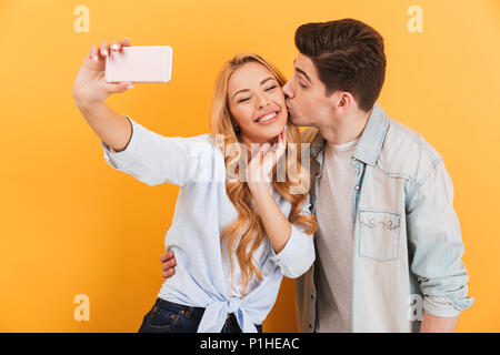 Portrait de joli couple taking photo selfies sur téléphone mobile tout en man kissing woman on joue plus isolé sur fond jaune Banque D'Images