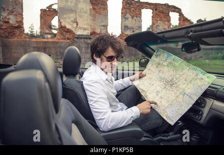 Beau jeune homme est titulaire d'une carte de route dans une voiture. Voyages et aventures concept. Tonique photo