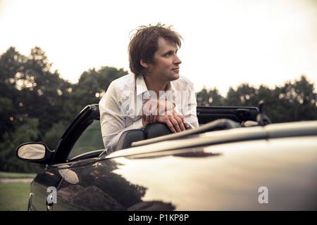 Beau jeune homme assis dans une voiture. Voyages et aventures concept. Tonique photo