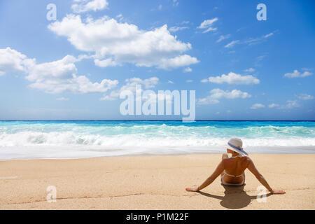 Femme assise sur la plage sauvage de l'île de Lefkada en Grèce Banque D'Images