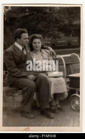 Italie - Vers les années 1940: Vintage photo montre un jeune couple avec landau. Couple est assis sur un banc dans le parc de la ville. Antique phtography noir & blanc. Banque D'Images