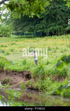 Glasgow, Ecosse, Royaume-Uni. 12 Juin, 2018. Météo France: un jeune homme, Jamie McKeown, pêche à la mouche sur les rives de l'eau Panier blanc sur un après-midi ensoleillé de Pollok Country Park. Credit: Skully/Alamy Live News Banque D'Images