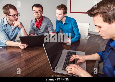 Les jeunes hommes qui sont affaires millénaire professionnels qui travaillent ensemble dans une salle de conférence dans un hôtel d'affaires moderne de haute technologie Banque D'Images