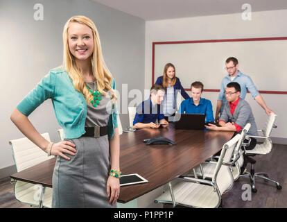 Une belle jeune femme d'affaires millénaire working on her tablet dans une salle de conférence avec ses collègues de travail, à Sherwood Park, Alberta, Canada Banque D'Images