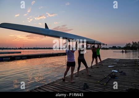 Les femmes de l'Hanlan Boat Club d'aviron de godille un lancement dans le lac Ontario à l'aube; Toronto, Ontario, Canada Banque D'Images