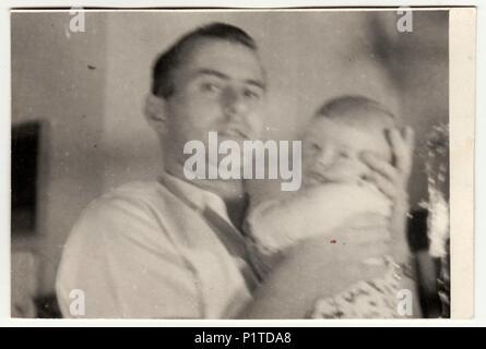 La République socialiste tchécoslovaque - circa 1950: Retro photo montre le père et d'enfant. Vintage Photographie noir et blanc. Avec grain de film original, le flou et les rayures. Banque D'Images