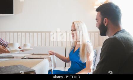 Heureux couple prend le menu au café Banque D'Images