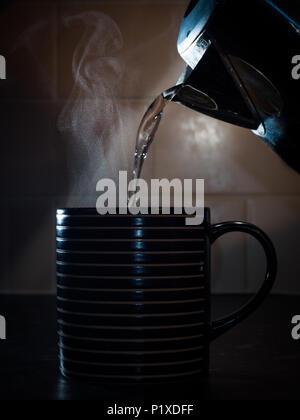 Étudier l'eau chaude provenant d'une électrique dans une tasse dans le kitichen Banque D'Images