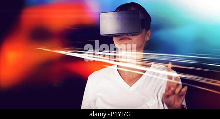 Jeune femme gesticulant pendant l'utilisation de casque de réalité virtuelle simulator Banque D'Images