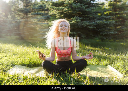 Photo de jeune athlète woman practicing yoga on rug Banque D'Images