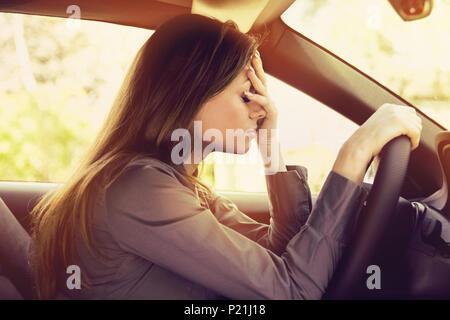 Souligné femme assis à l'intérieur sa voiture Banque D'Images