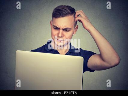 Jeune homme à la perplexe lors de l'utilisation d'ordinateur portable ayant des difficultés avec l'appareil. Banque D'Images