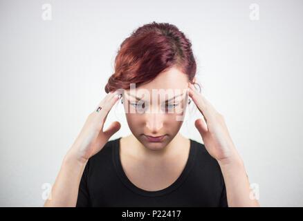Une jeune fille avec des expressions du visage, et les mains montre que la douleur est le mal de tête, maux de tête, douleur, fond blanc, les expressions du visage Banque D'Images