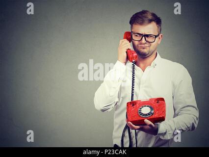 Homme à lunettes en conversation sur le téléphone à l'ancienne à l'écart dans l'incompréhension. Banque D'Images