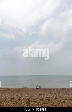 Les filles à la recherche de couple isolé de l'horizon à Hastings Beach, Hastings, East Sussex, Angleterre , Royaume-Uni Banque D'Images
