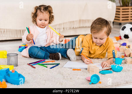 Frères et soeurs adorable dessin sur un étage avec des crayons de couleur Banque D'Images