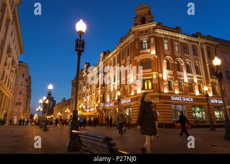 Moscou, Russie - le 21 septembre 2017: les gens et bâtiment historique décoré par une lumière chaude à l'Arbat de walking street pendant le crépuscule avec ciel bleu. Banque D'Images
