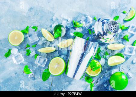 Shaker bar et télévision accessoires jeter. Mojito cocktail ingrédients frais, menthe, citron vert et des glaçons sur un fond noir en gris. Boisson d'été concept avec