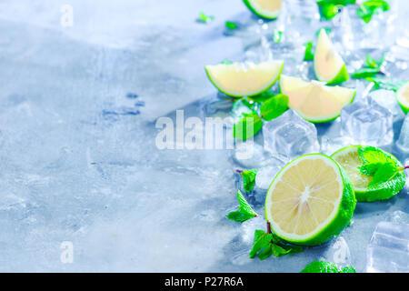 Menthe, citron vert et des glaçons, mojito cocktail Ingrédients en-tête avec copie espace. Boissons rend l'été close-up. La lumière du soleil et fraîcheur concept. Banque D'Images