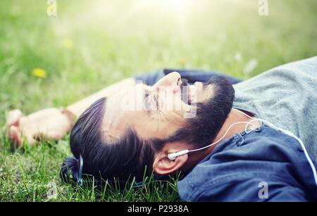 Man with earphones écouter de la musique sur l'herbe Banque D'Images