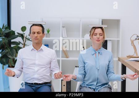 Businesspeople méditer avec des livres sur la tête à un bureau moderne Banque D'Images