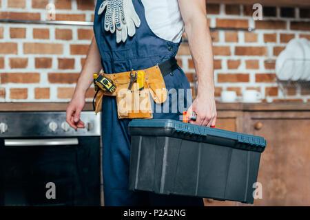 Cropped shot of home master avec ceinture d'outils qui maintient la boîte à outils Banque D'Images