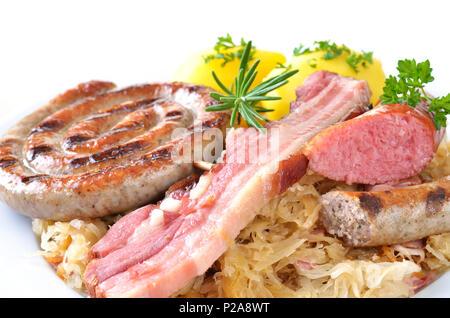 Ventre de porc et saucisses diverses sur la choucroute avec des pommes de terre, fond blanc Banque D'Images