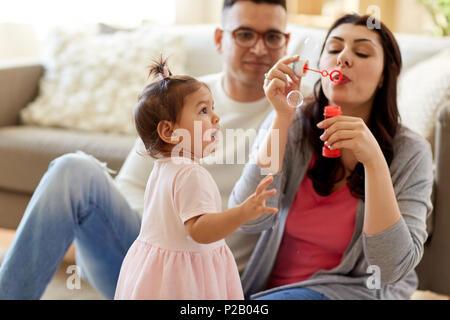 Famille avec des bulles de savon jouant à la maison Banque D'Images