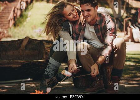 Heureux l'homme et la femme assis par le feu et griller des guimauves sur bois au camping. Couple ayant un grand temps sur leur camping. Banque D'Images