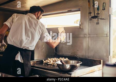 Jeune chef cuisiner certains de ses plats préférés dans un camion alimentaire. L'homme préparer les aliments sur la cuisinière dans son camion alimentaire. Banque D'Images