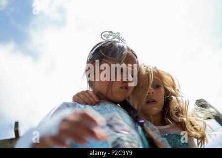 Jeune fille asiatique vêtue d'une robe de princesse et une tiare de célébrer son anniversaire avec sa meilleure amie hugging son Banque D'Images