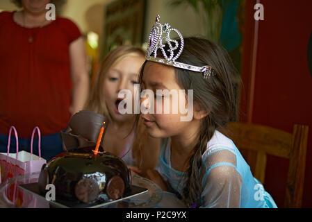 Cute little preteen Asian girl portant une robe de princesse et une tiare soufflant les bougies sur son gâteau d'anniversaire avec son meilleur ami assis avec elle Banque D'Images